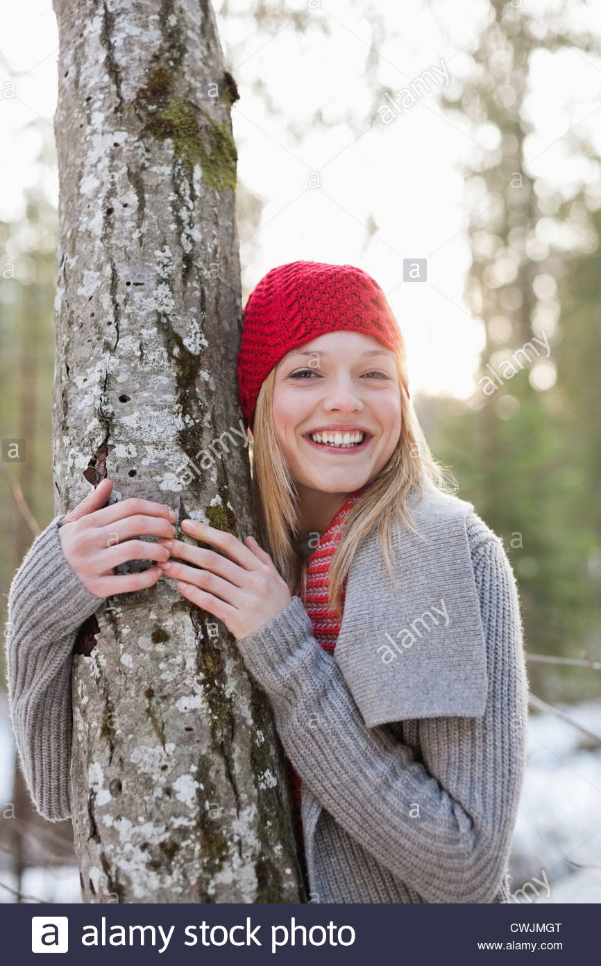 Portrait of smiling woman in red knit hat hugging tree trunk - Stock Image