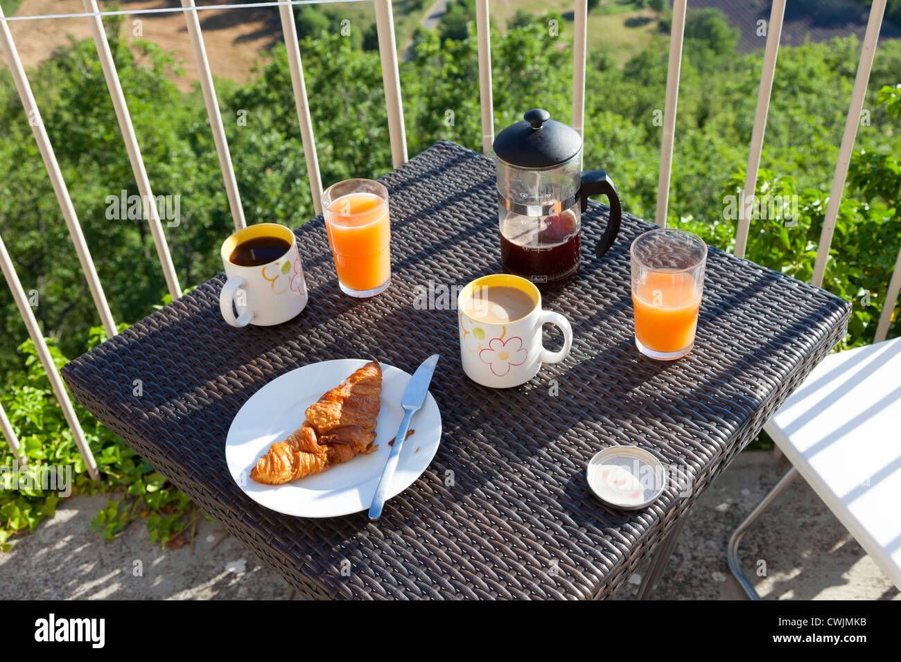 Breakfast on balcony with coffee, ornage juice and croissants - Stock Image