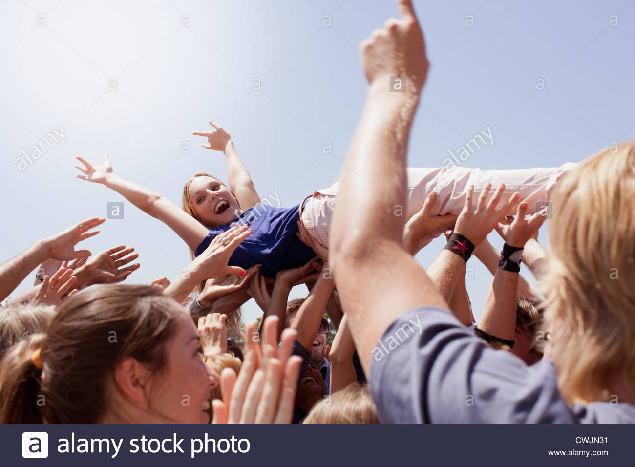 Enthusiastic woman crowd surfing - Stock Image