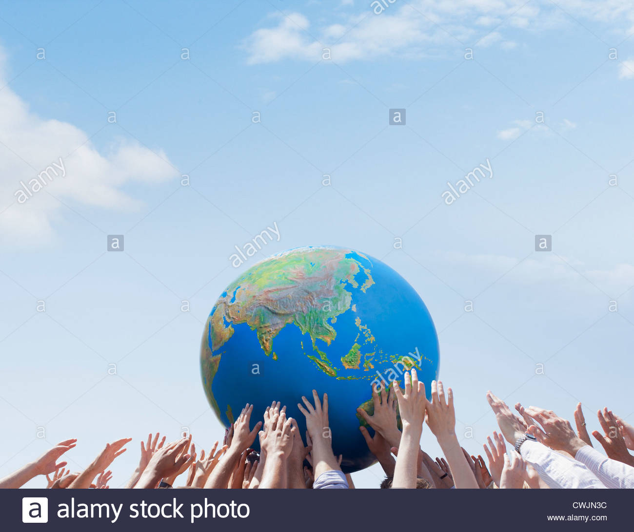 Crowd reaching for globe - Stock Image