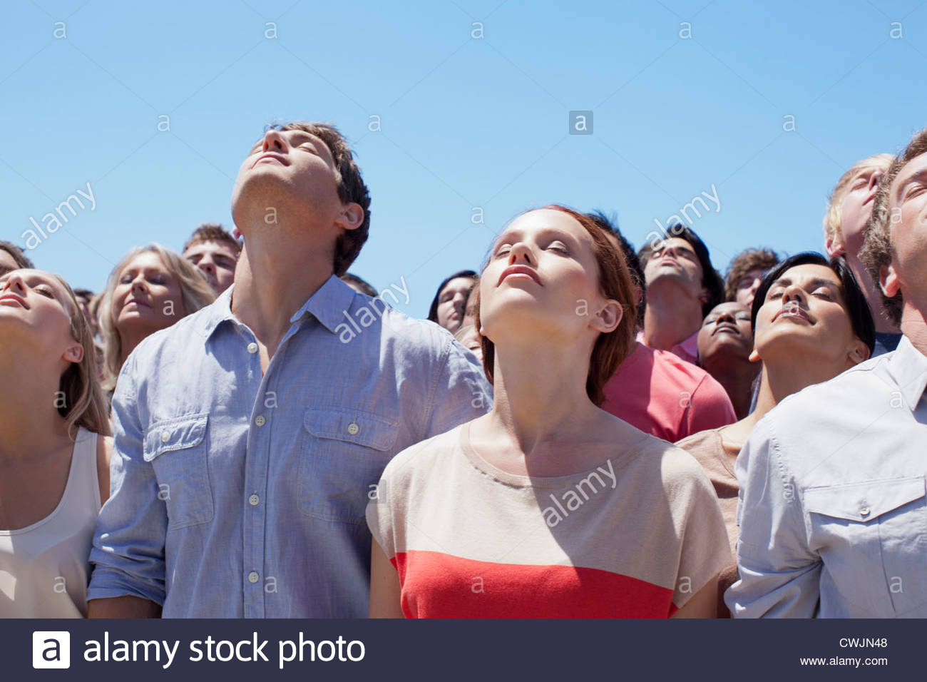 Serene people with heads back in crowd - Stock Image
