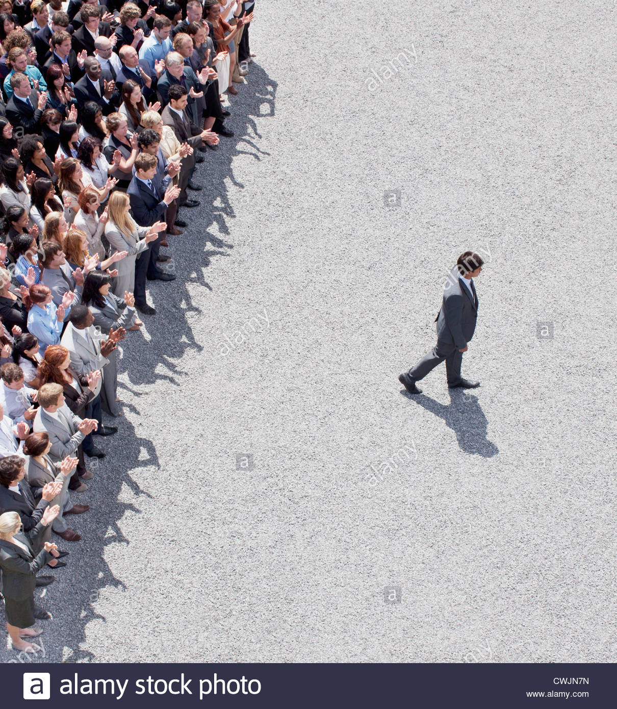 Businessman walking away from clapping crowd - Stock Image