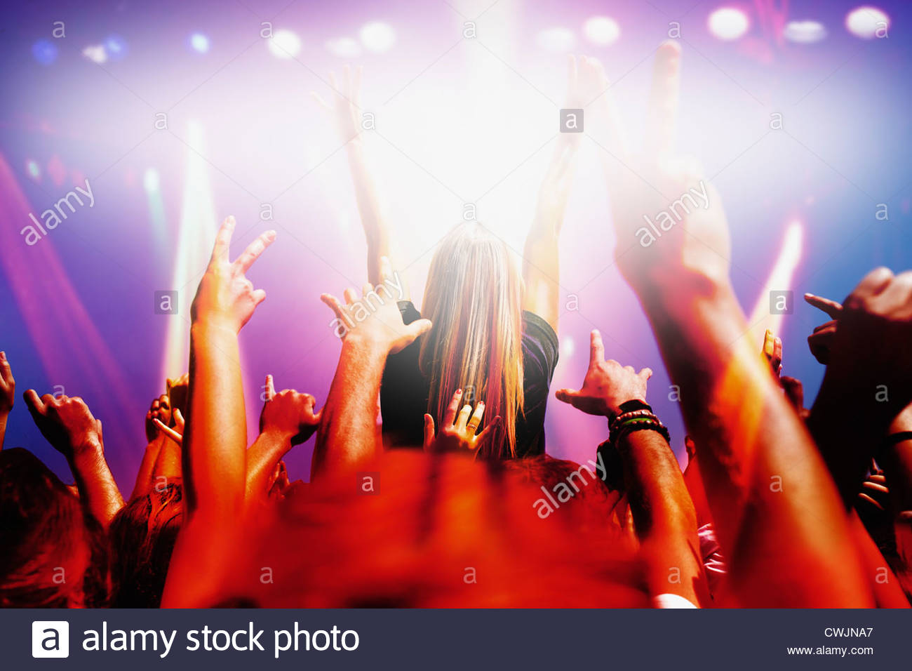 Stage lights shining on audience with arms raised at music concert - Stock Image