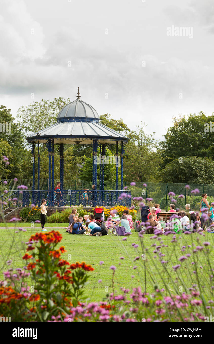 Family's enjoying the sunshine around the bandstand at the War Memorial Park at Romsey - Stock Image