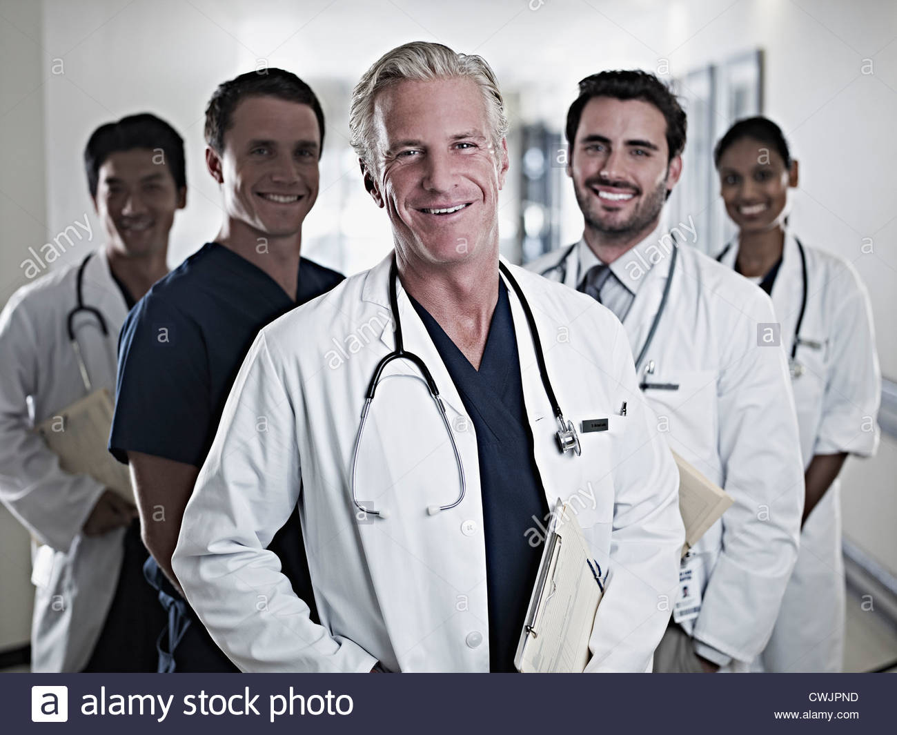 Portrait of smiling doctors and nurse in hospital corridor - Stock Image