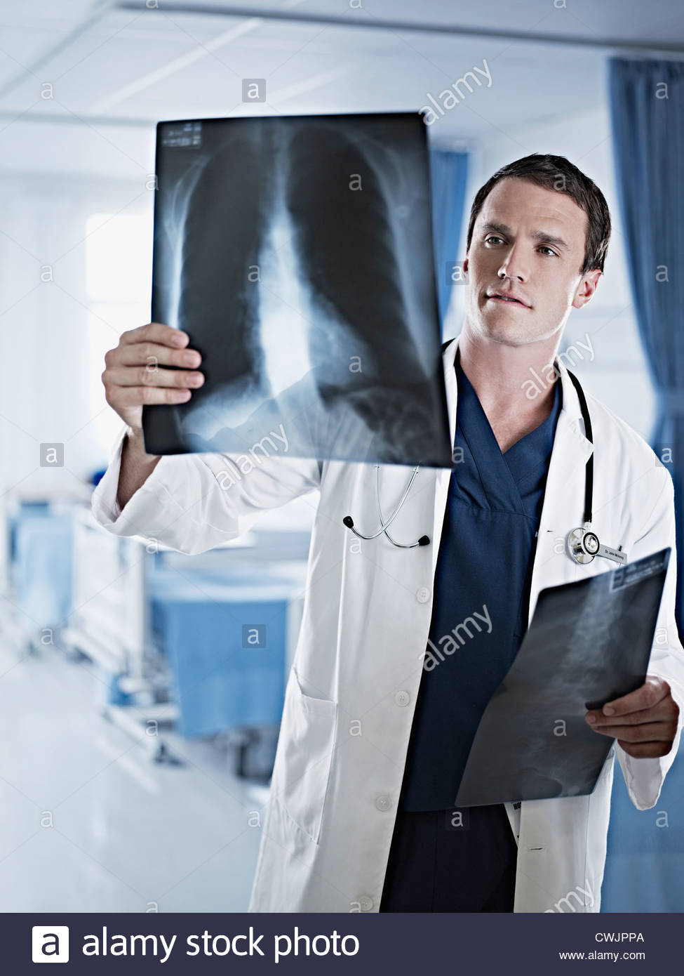 Doctor examining x-rays in hospital room - Stock Image