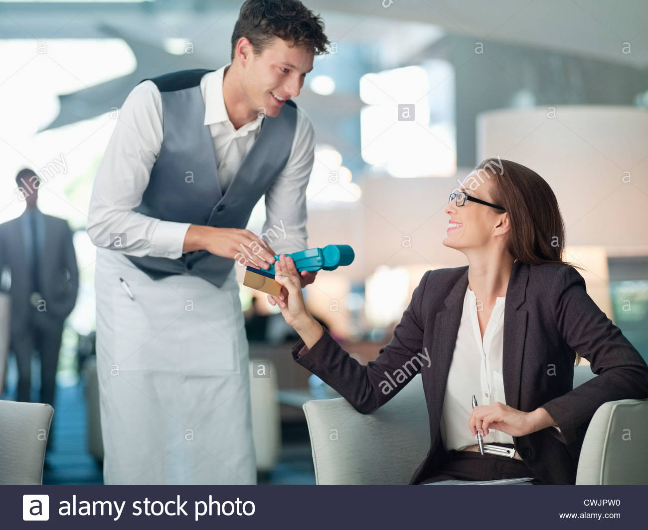 Waiter processing businesswoman's credit card with credit card reader Stock Photo
