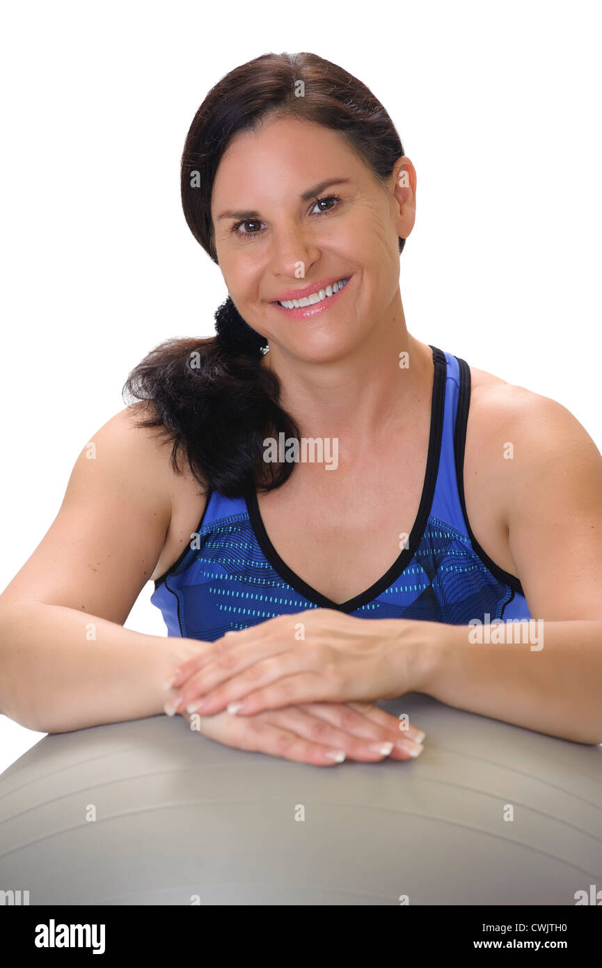 Portrait of a beautiful brunette woman in her 40s wearing blue workout clothing, smiling and leaning on a gray exercise - Stock Image
