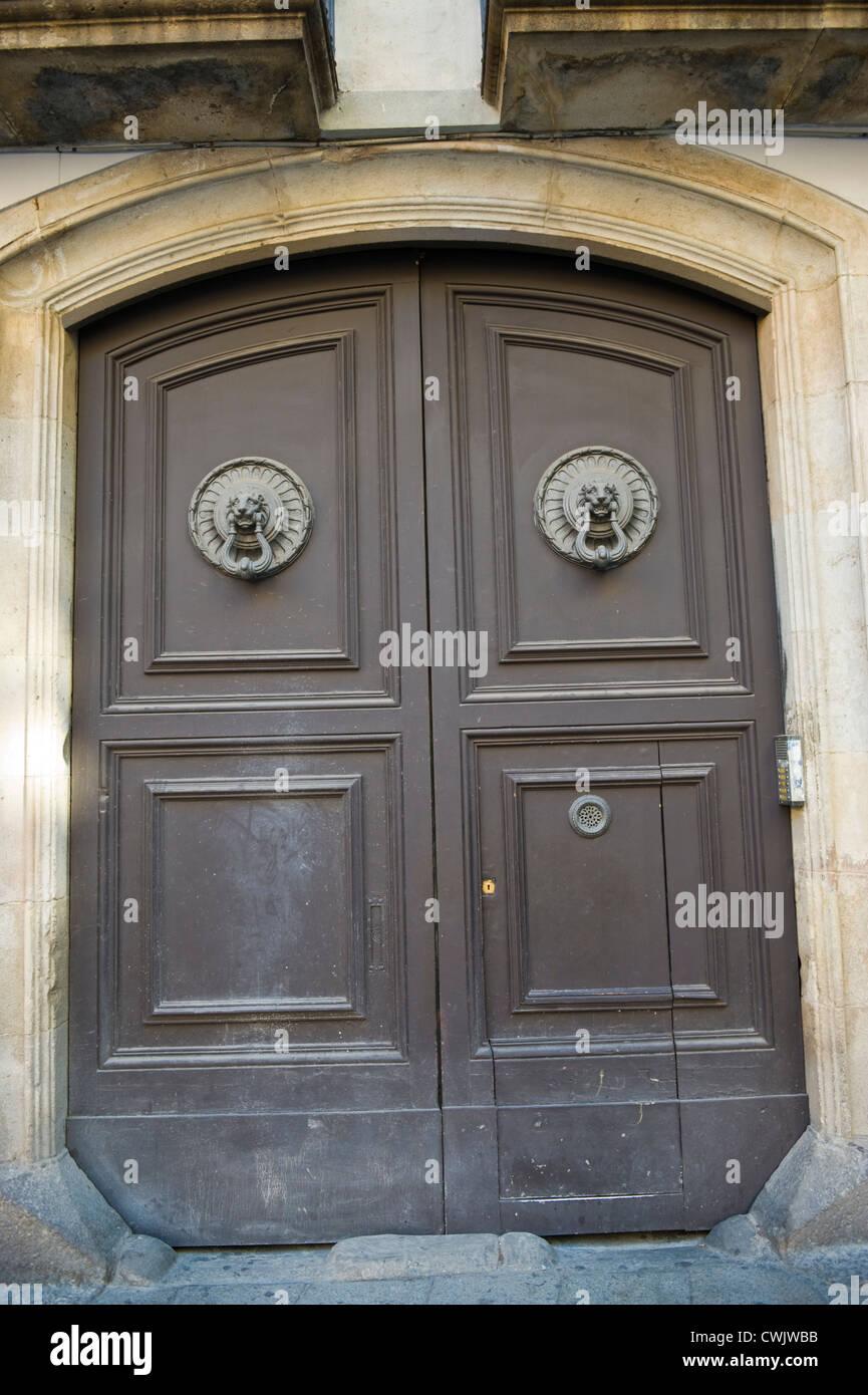 Huge wooden front door with big knockers of apartment building in Barcelona Catalonia Spain ES & Huge wooden front door with big knockers of apartment building in ...