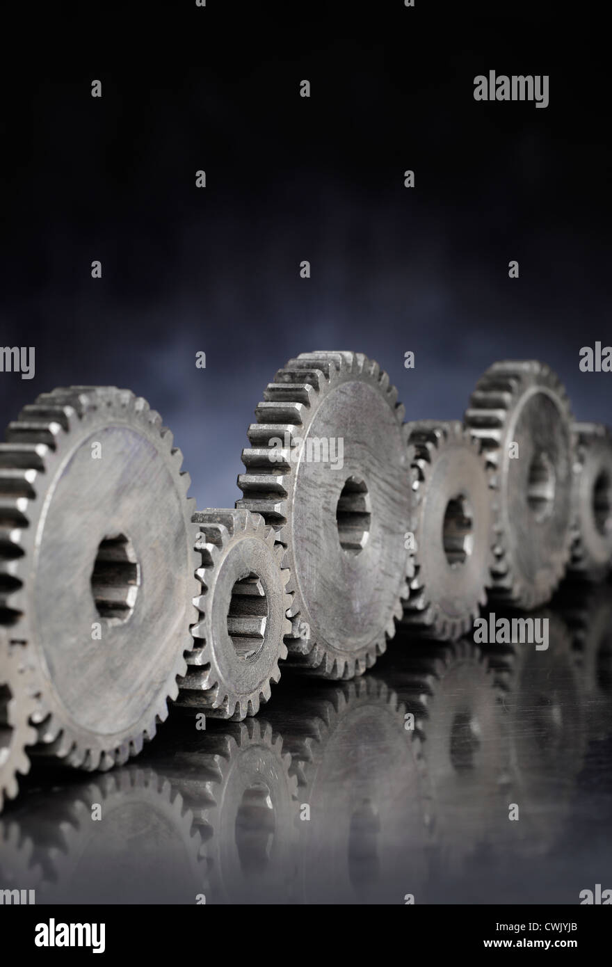 Old metallic cog gears in a row. - Stock Image