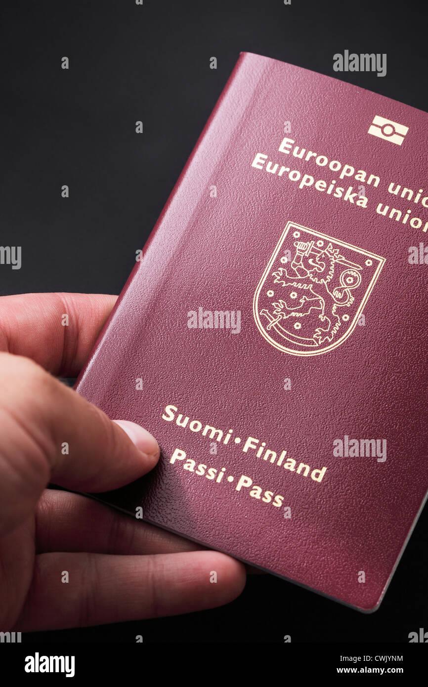 Man holding finnish passport in his hand. - Stock Image