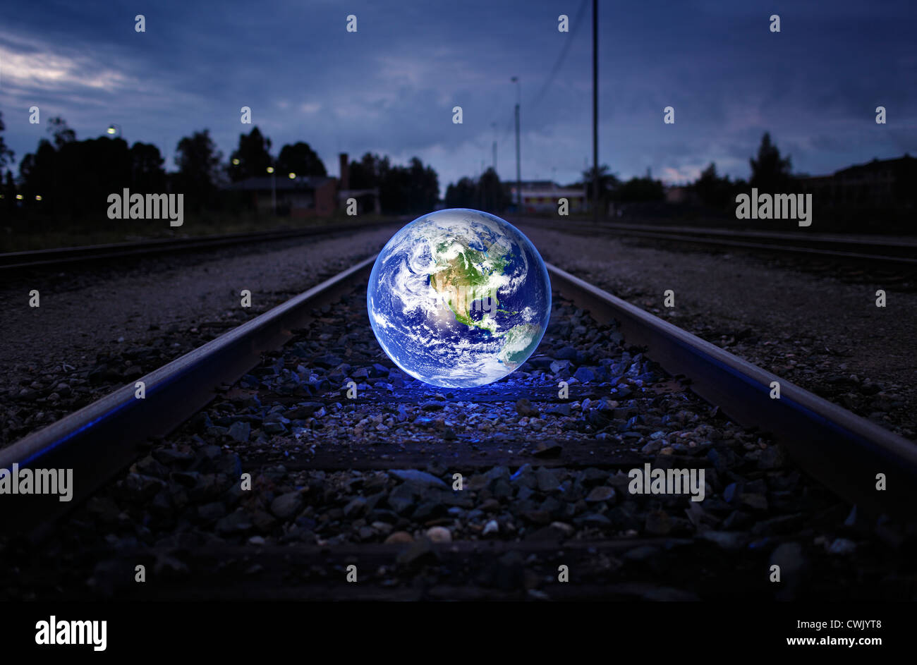Glowing earth on an old railroad track. Earth image provided by NASA. - Stock Image