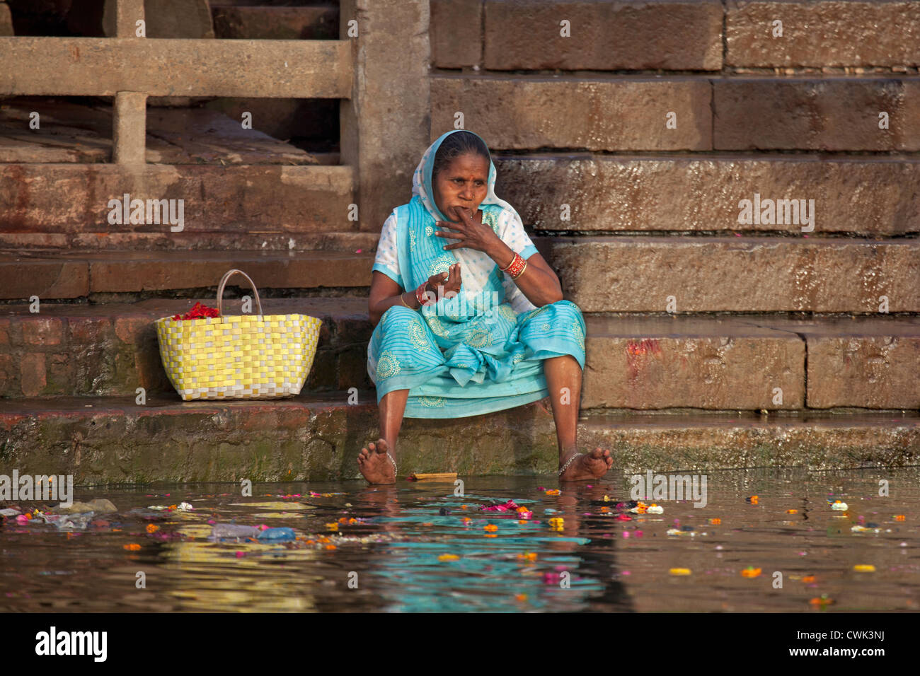 Old Indian woman cleaning her teeth with finger in dirty polluted water of the Ganges river at Varanasi, Uttar Pradesh, - Stock Image