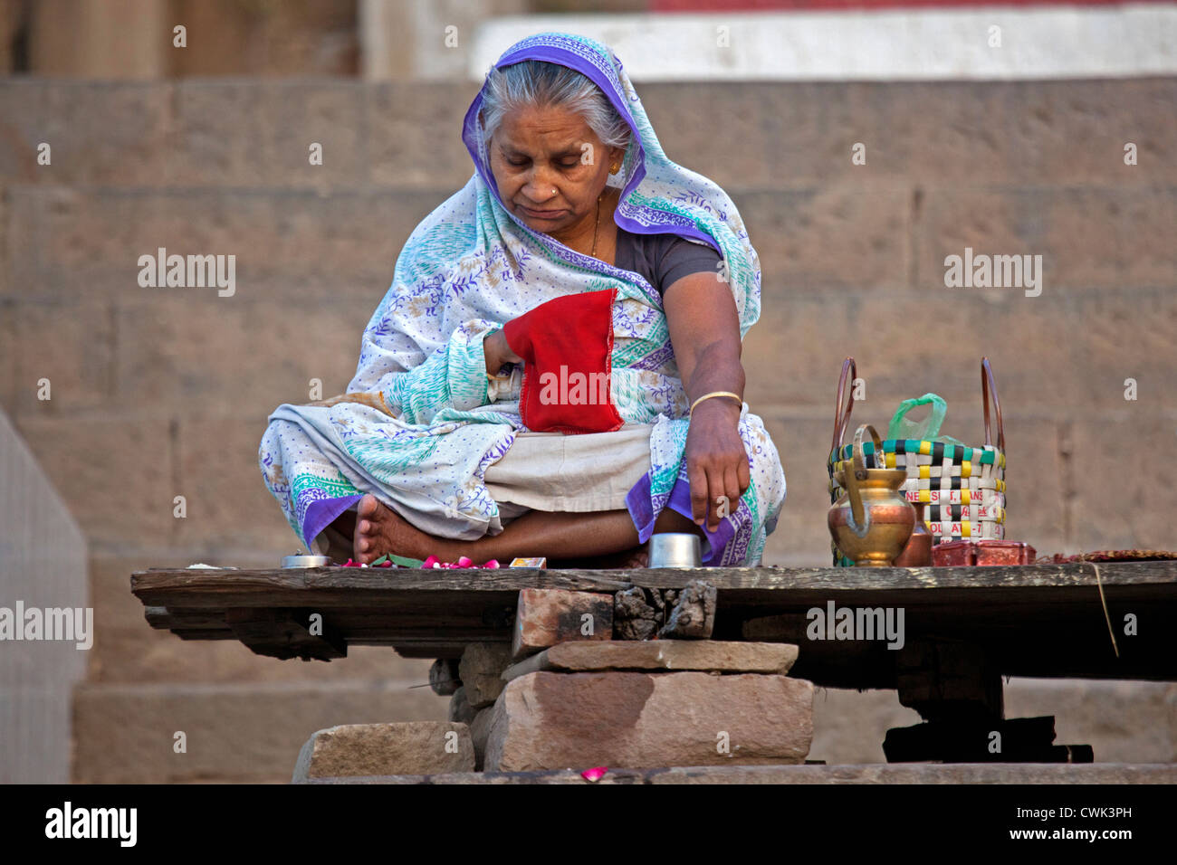 Old Indian woman sitting on ghat and praying near the Ganges river at Varanasi, Uttar Pradesh, India - Stock Image