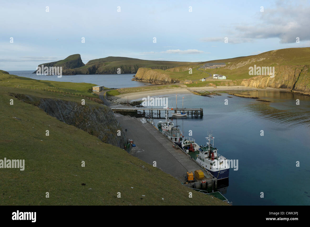 Mail boat Good Shepherd IV on the pier in North Haven on Fair Isle, Shetland, with Sheep Rock in distance. June - Stock Image