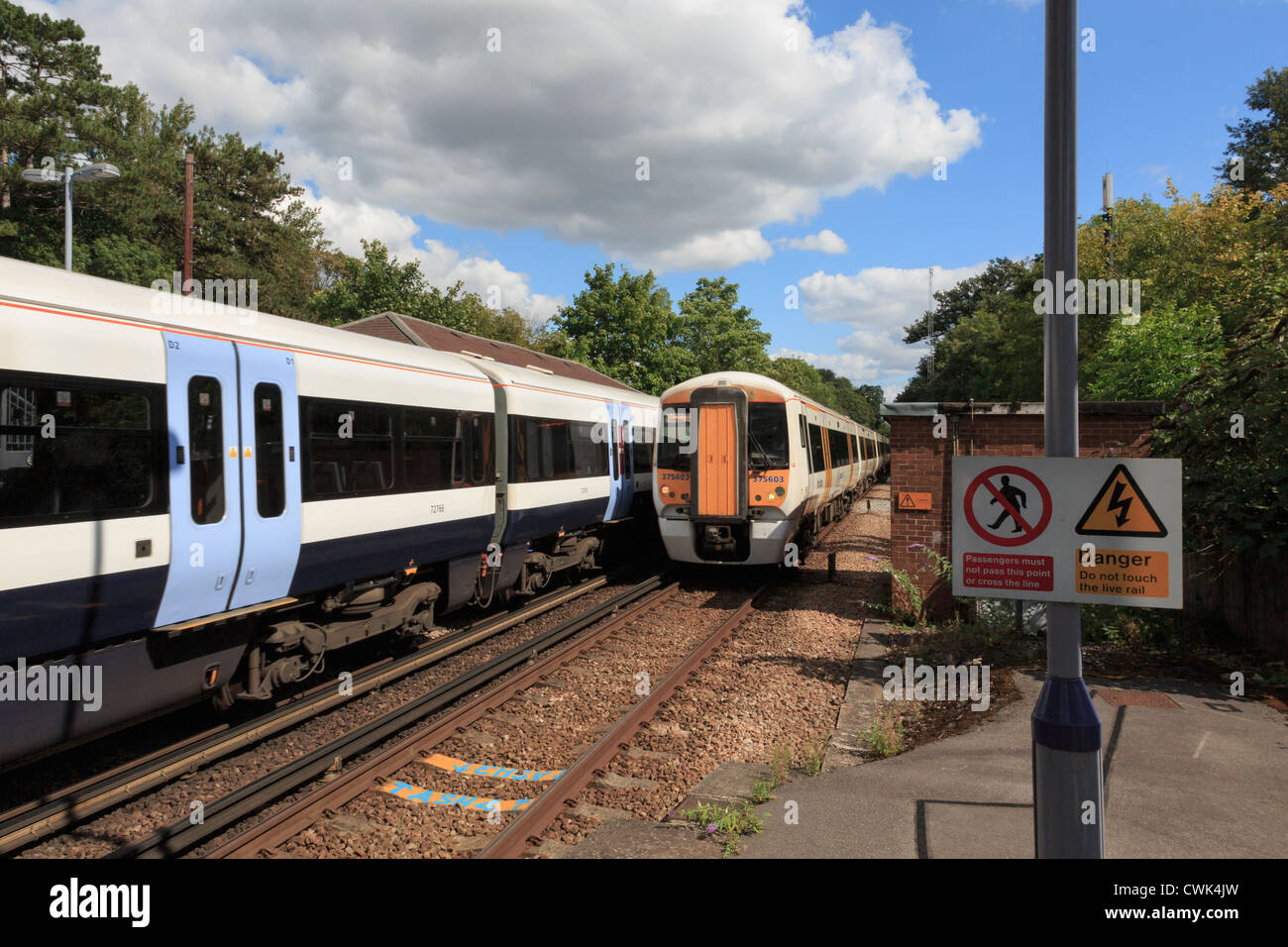 Two electric express trains passing on electrified railway with danger sign warning not to cross tracks. England - Stock Image