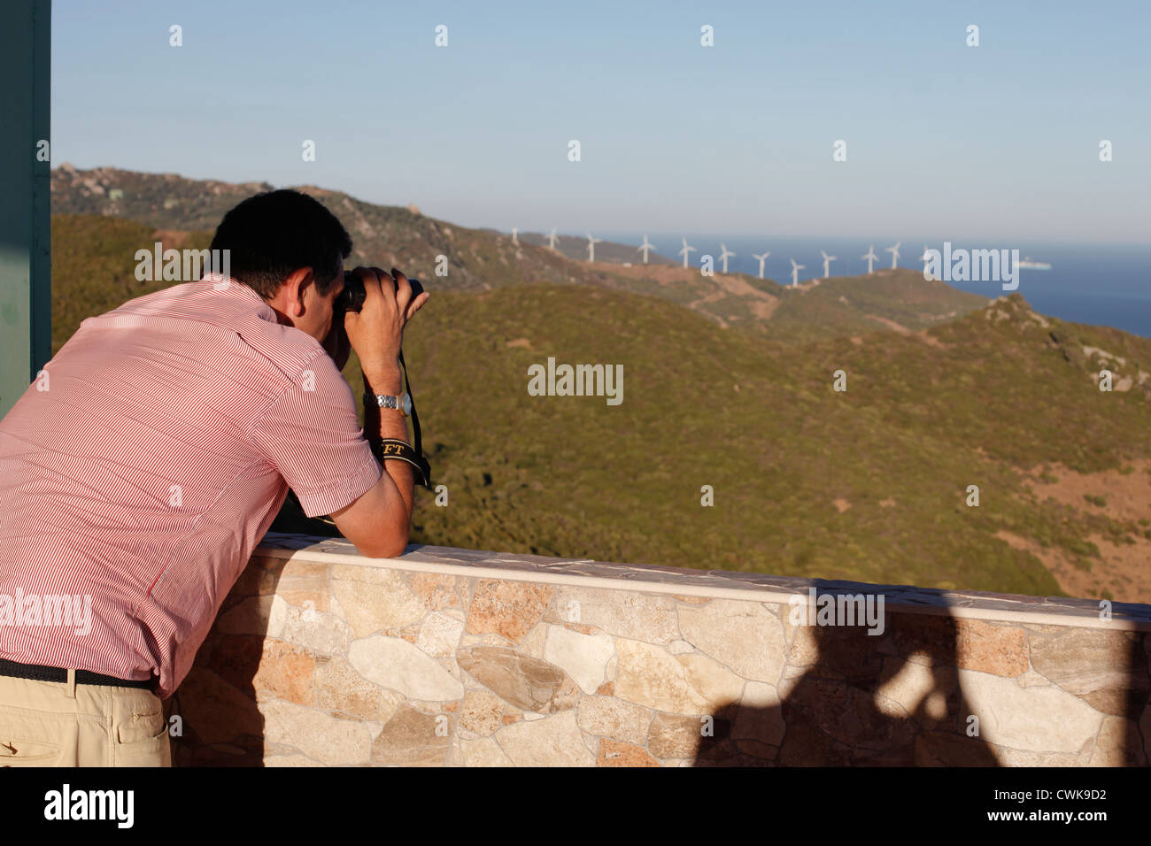 A man uses binoculars to see Africa at the viewpoint of Tarifa - Stock Image