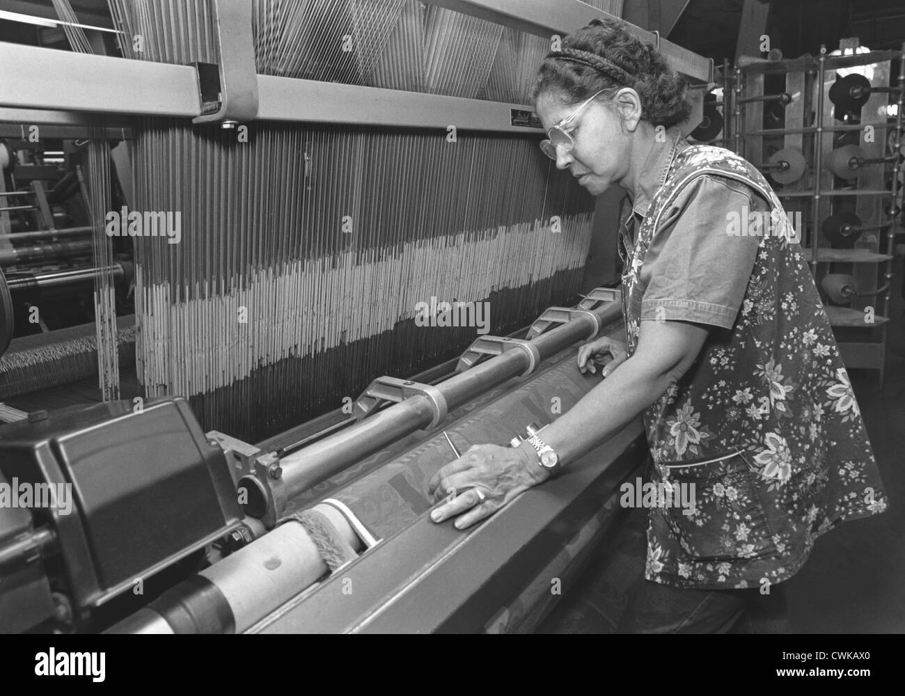 A woman, textile worker, working with her hands in a clothing and fabric factory. - Stock Image