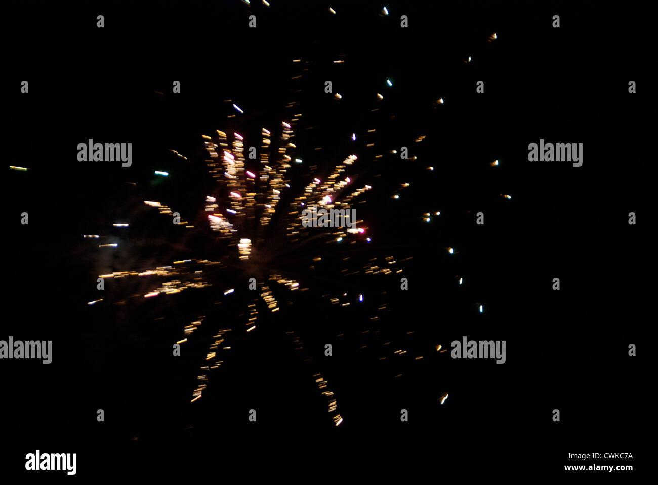 Fire works exploding against dark sky - Stock Image
