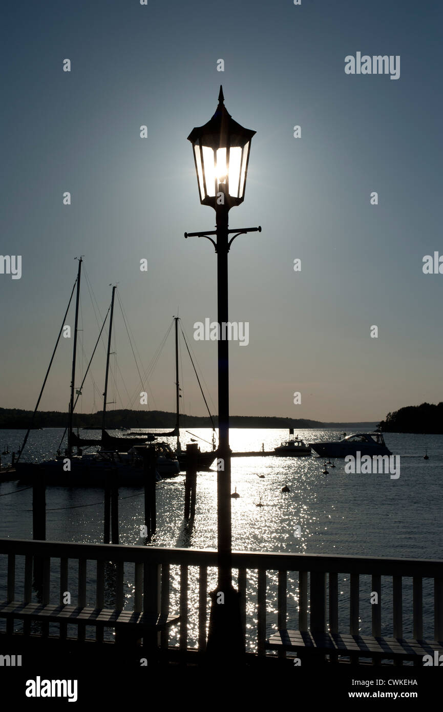 Sun lighting up the light in a lamp post in a harbor with boats in the background - Stock Image
