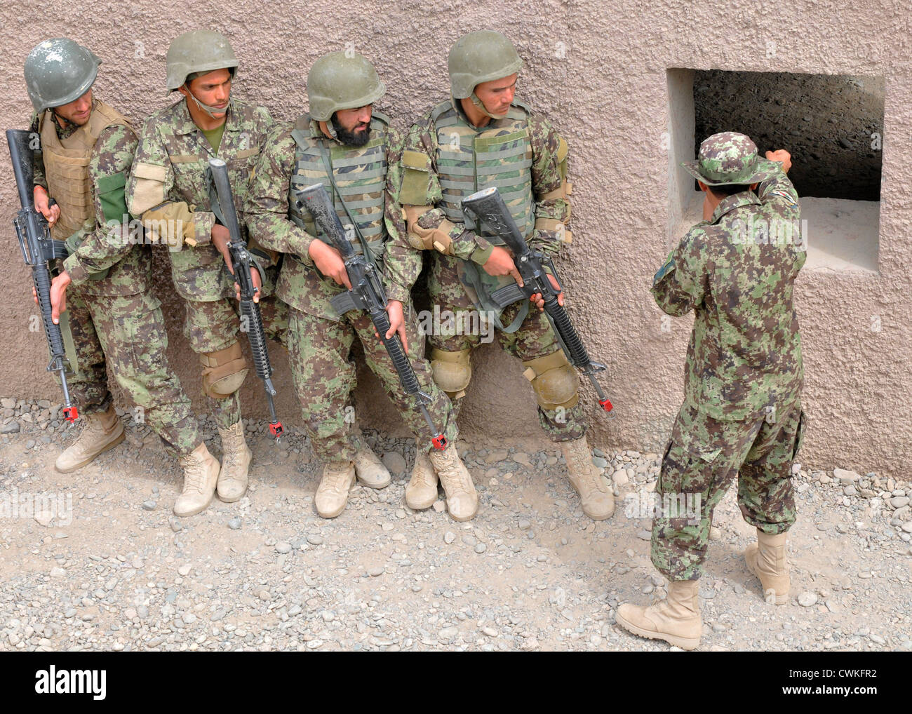 An Afghan National Army team leader course teacher instructs ANA soldiers on room clearing procedures during the - Stock Image