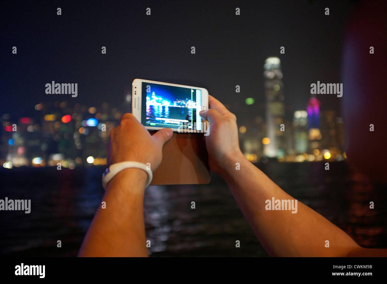 A tourist using a Samsung galaxy recording a video of Hong Kong harbor. - Stock Image
