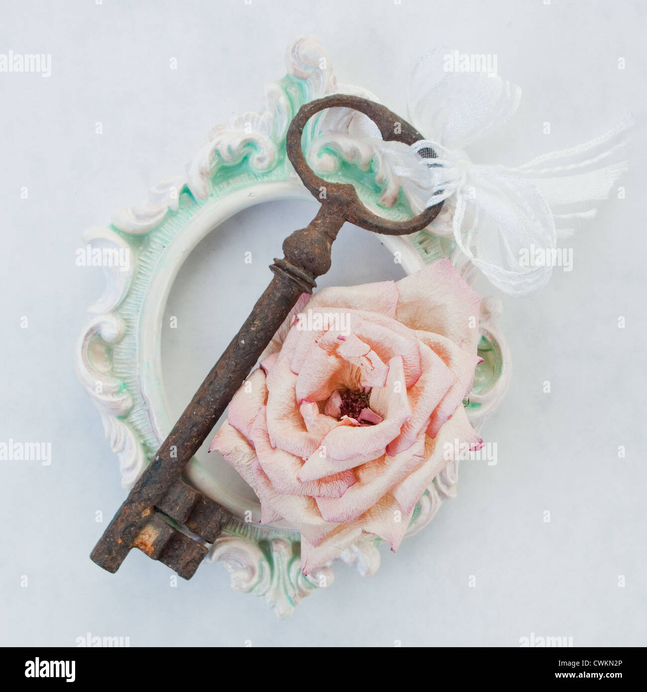 antique, rusty key on an old, vintage frame with dry roses - Stock Image