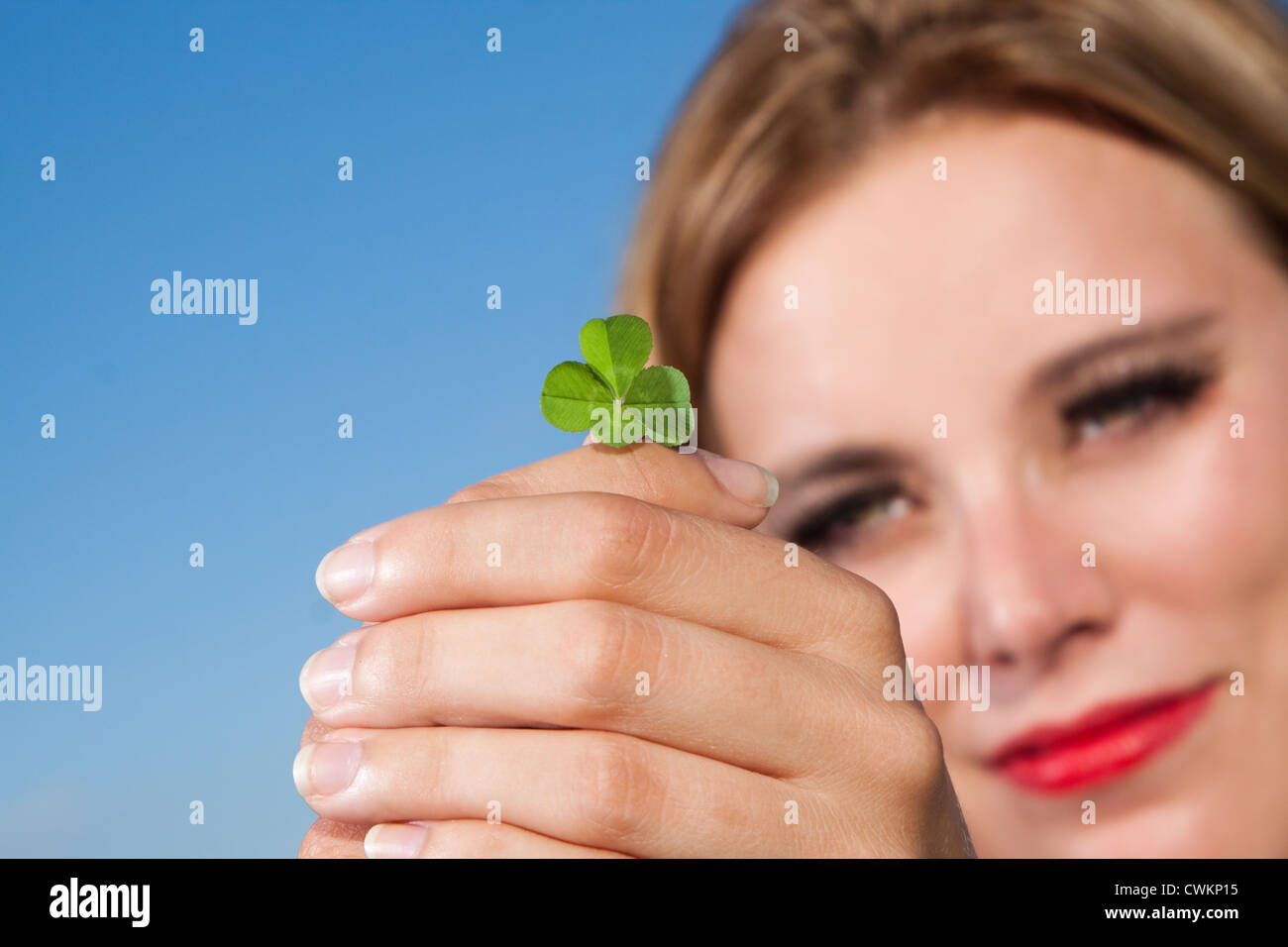 woman with four leafed clover - Stock Image