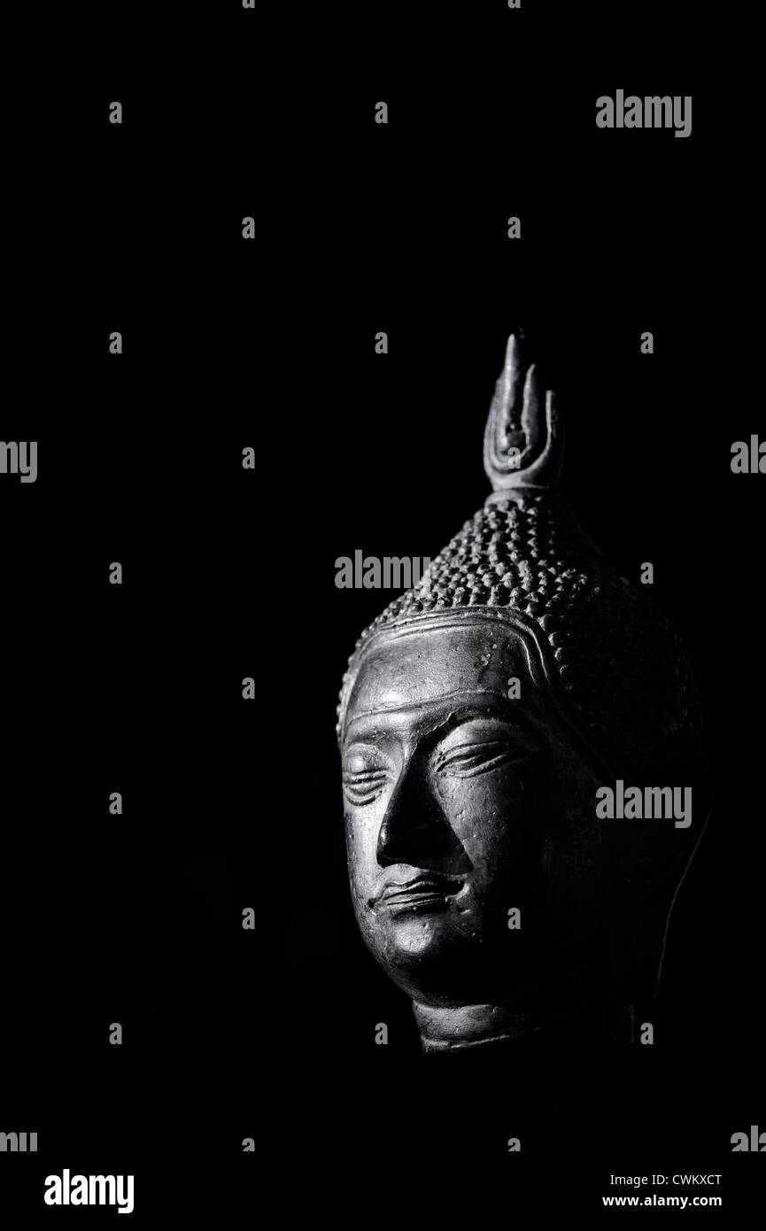 Buddha head statue on black background. Black and White - Stock Image