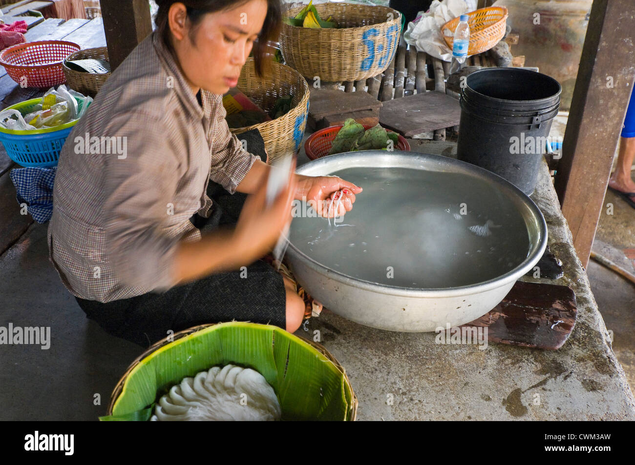 Horizontal close up portrait of a Cambodian woman making rice noodles, kh'teaw, in basic surroundings. - Stock Image