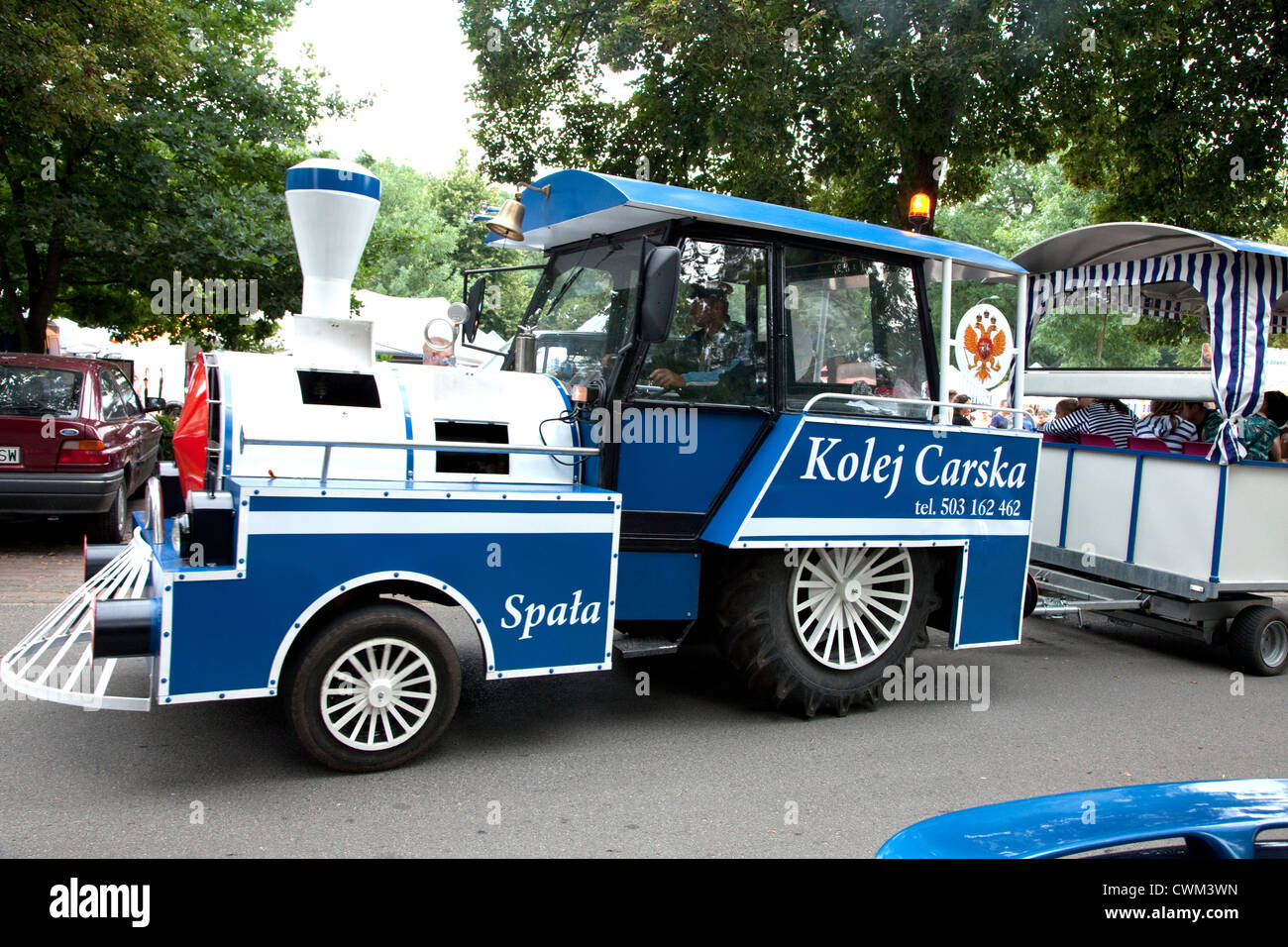 Railroad like engine pulling trailer of sightseers around country fair (Rynek). Spala Central Poland - Stock Image