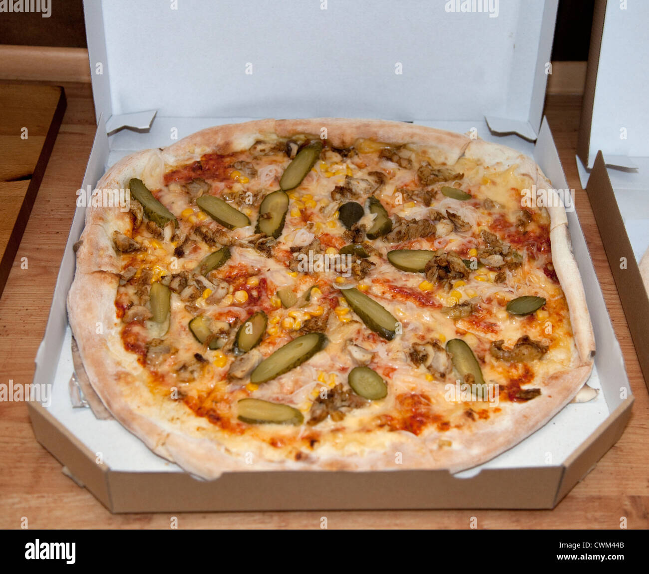 Polish pizza with plenty of pickles corn and cheese delivered in a cardboard box. Lodz Central Poland - Stock Image
