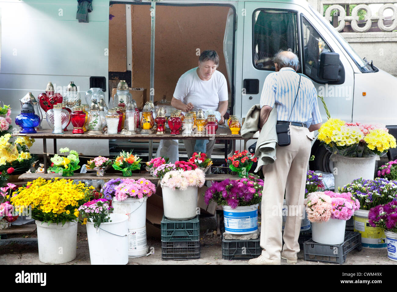 Purchasing flowers outside cemetery gates. Roman Catholic Church's Cemetery Cmentarz Rzymskokatolicki Lodz Central - Stock Image