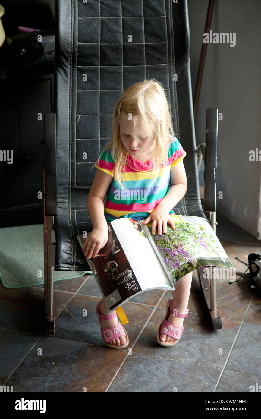 Polish girl age 4 reading magazine in her summer home. Zawady Central Poland - Stock Image