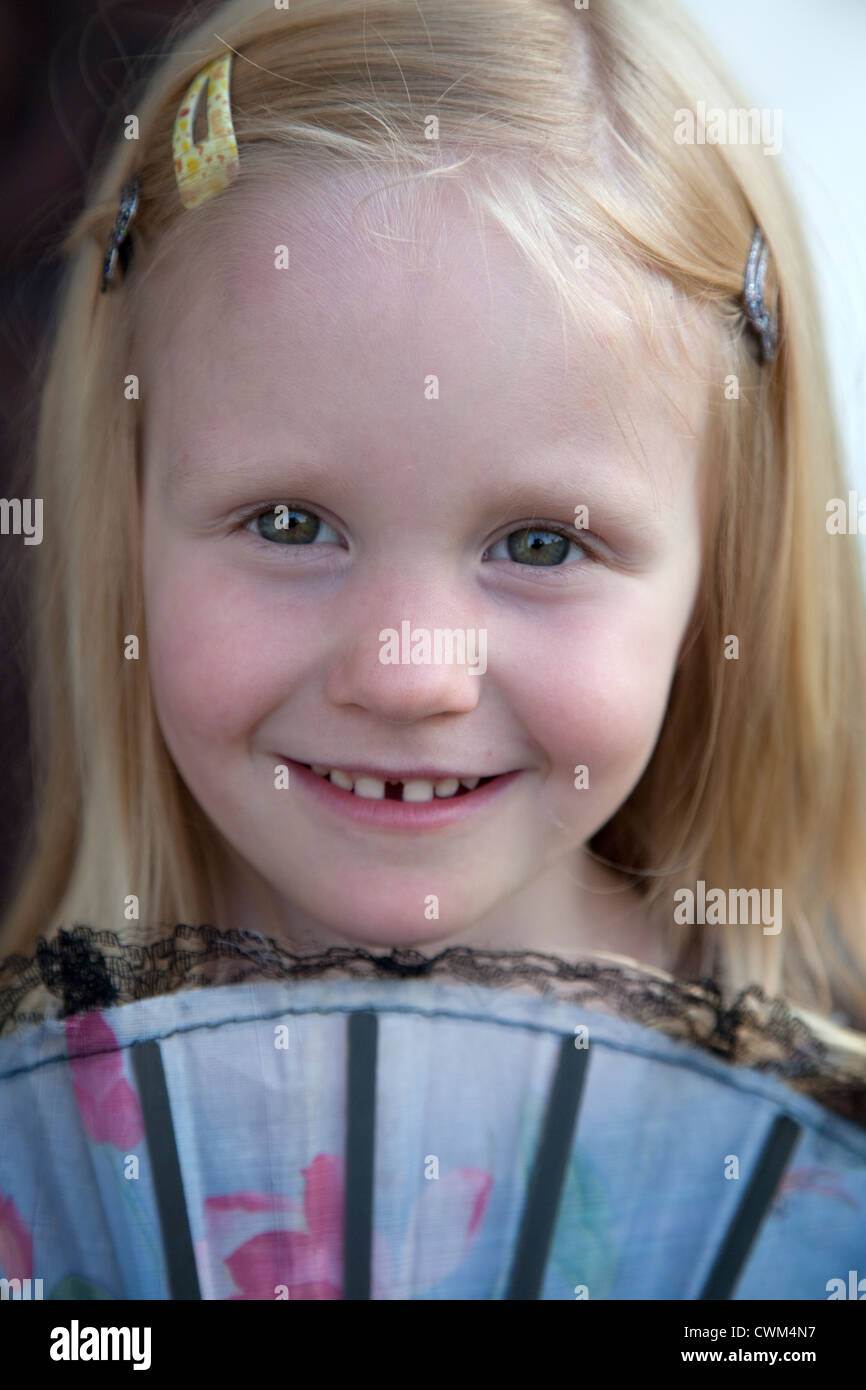 Happy Polish girl age 4 looking over the top of a traditional hand-held folding fan. Zawady Central Poland - Stock Image