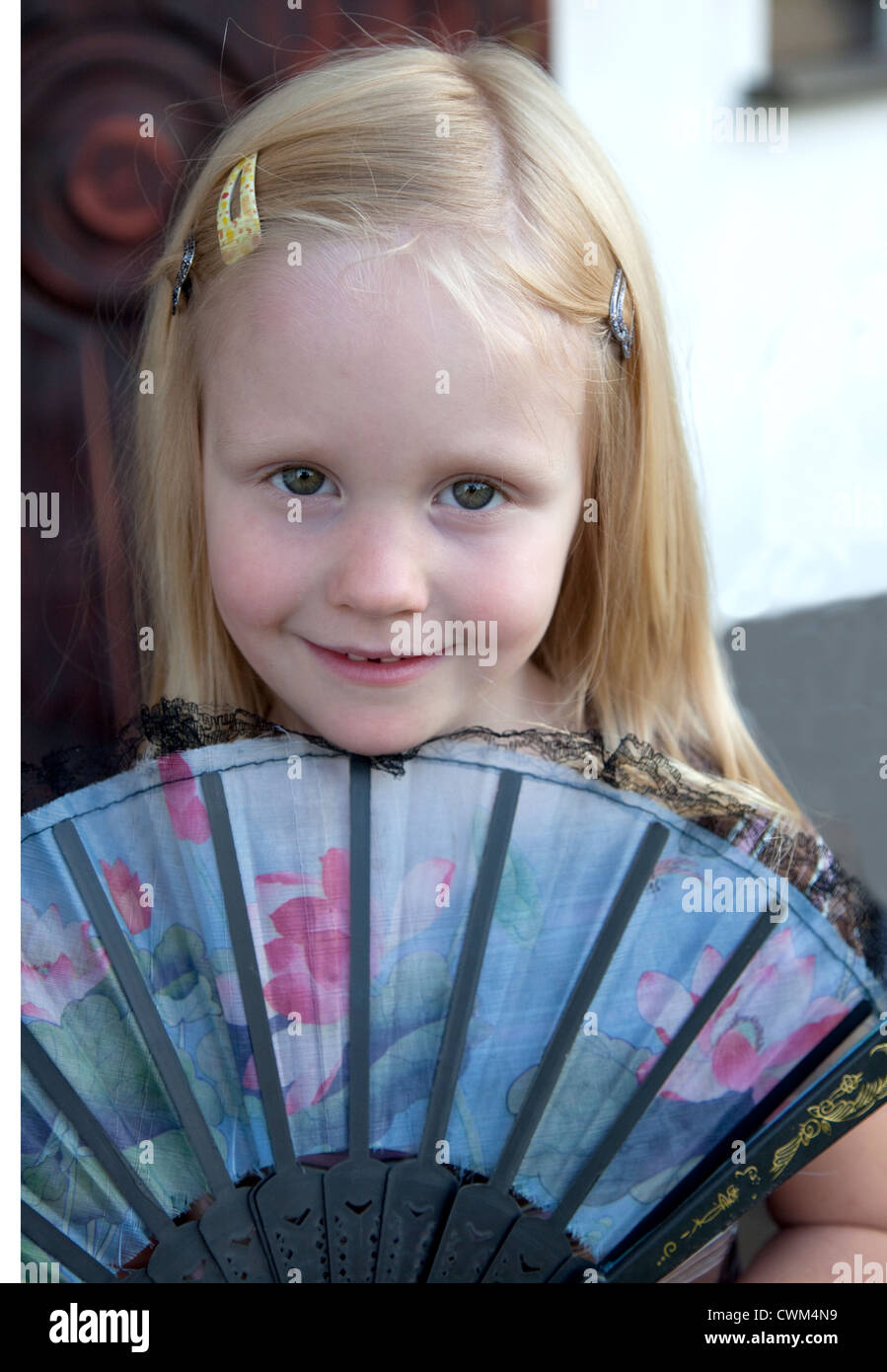 Polish girl age 4 looking over the top of a traditional hand-held folding fan. Zawady Central Poland - Stock Image
