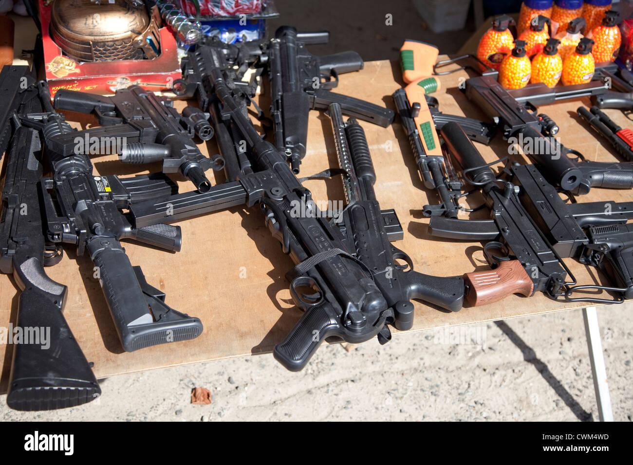 Replica assault rifles, guns and grenades for sale at sidewalk flea market. Rzeczyca Central Poland - Stock Image