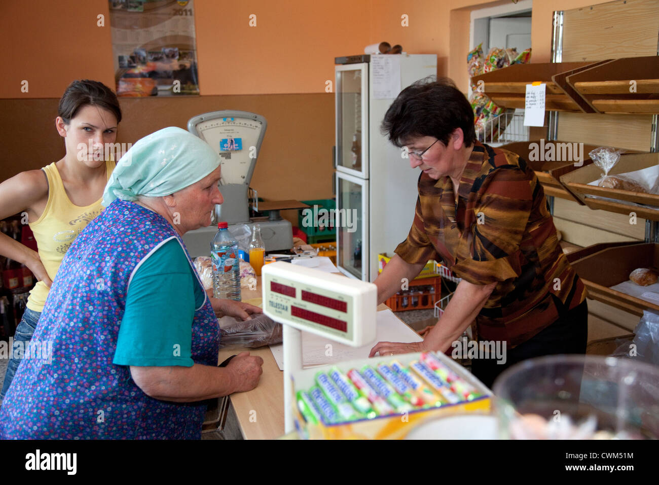 Impatient teen girl overseeing her grandma's shopping trip to village grocery store age 16, 85 and 50. Mala - Stock Image