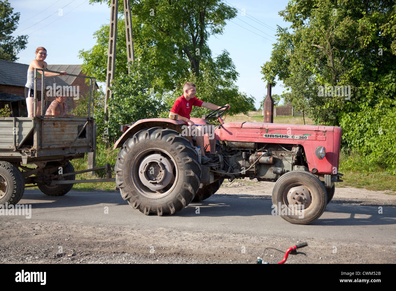 Polish man driving tractor and cart carrying two women along village lane. Mala Wola Central Poland Stock Photo