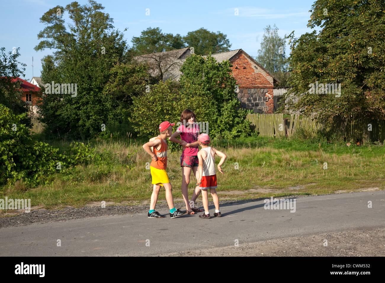 Polish children talking on village road. Mala Wola Central Poland - Stock Image