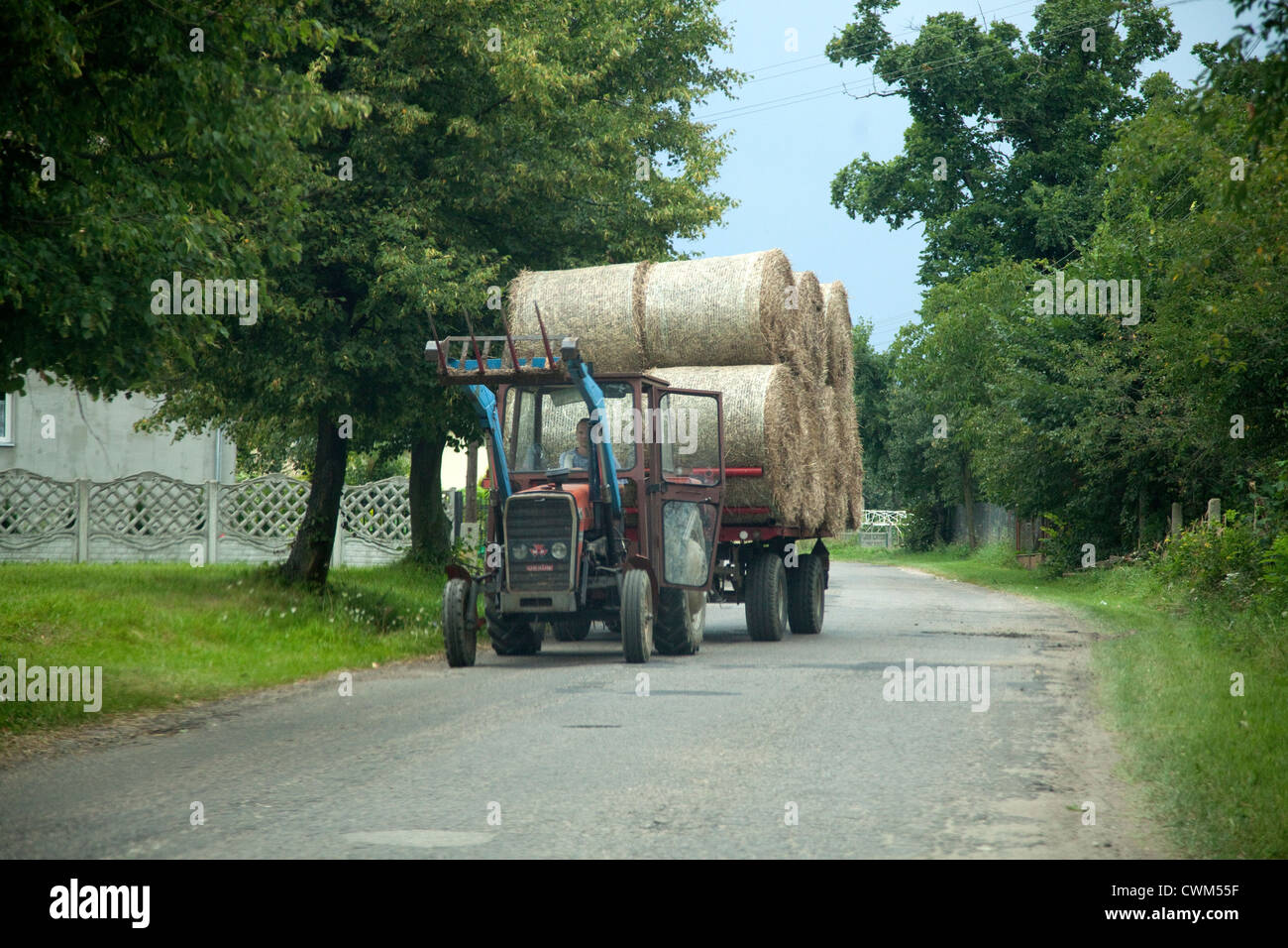 Cart full of farmers hay bails transported down village lane. Zawady Central Poland - Stock Image