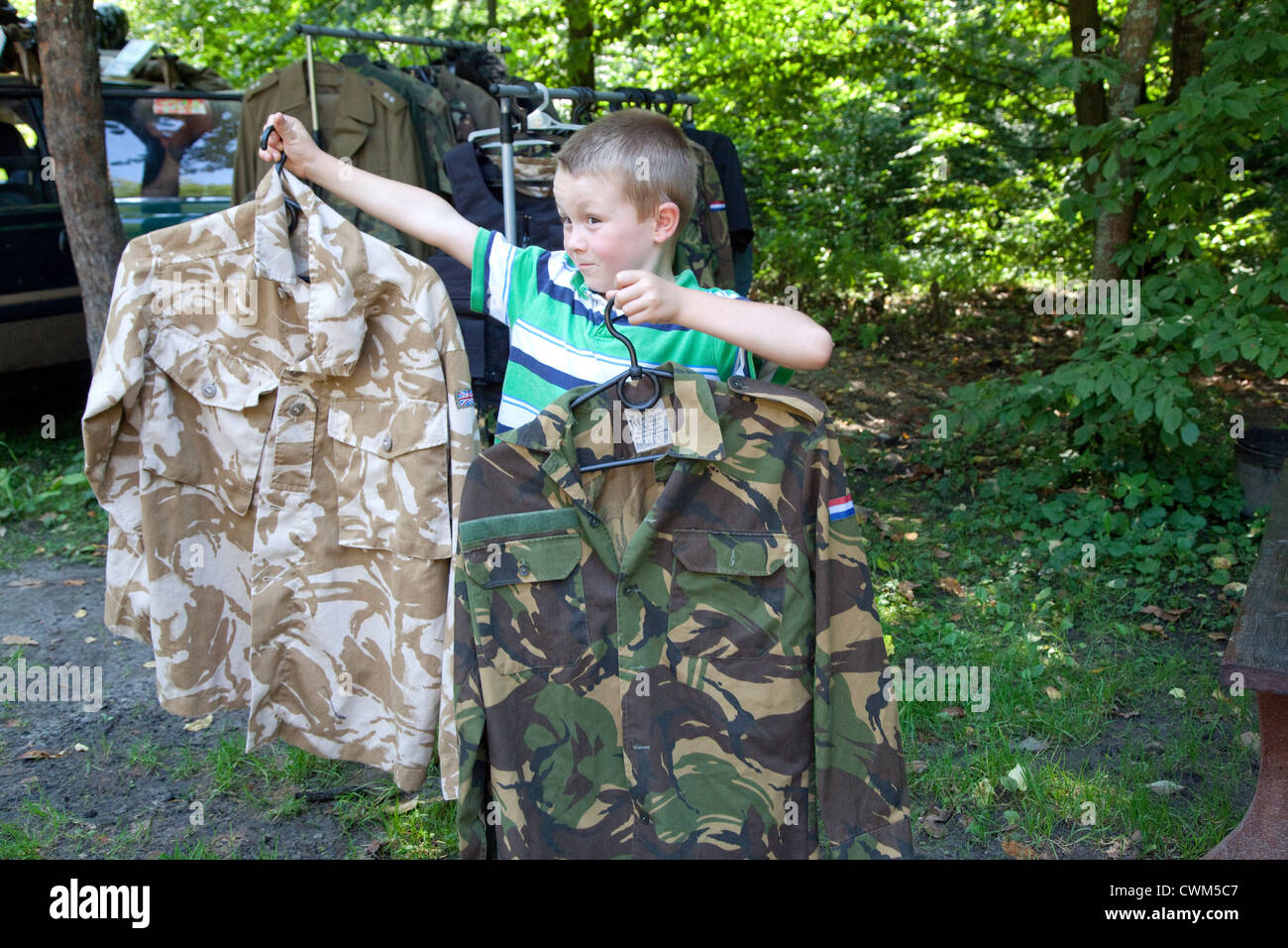 Boy age 6 displaying camo military jackets for sale at Hitler's Bunker. Konewka Central Poland - Stock Image