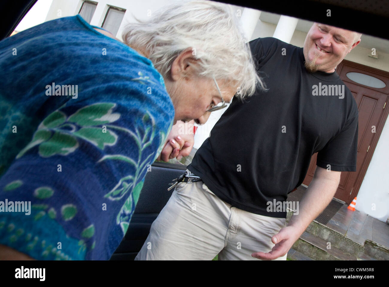 Good natured grandson pulling ensconced grandmother from car after ride to neighbors house age 86 and 37. Zawady - Stock Image
