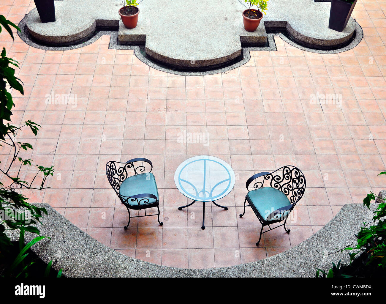 Two garden chairs against brick wall - Stock Image