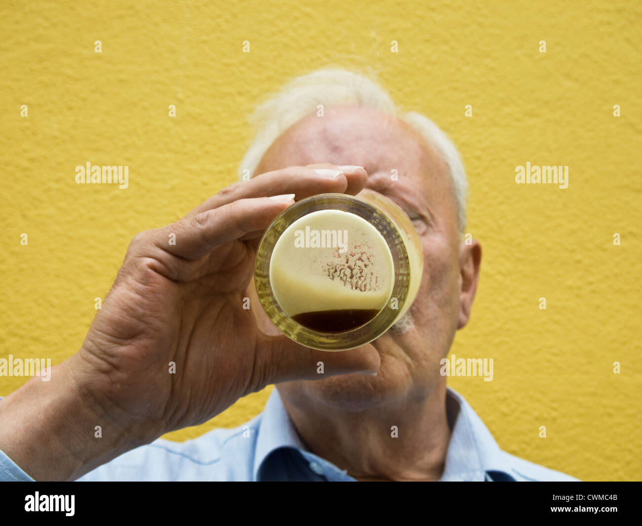 A man drinking the last dregs of a pint of Guinness beer - Stock Image