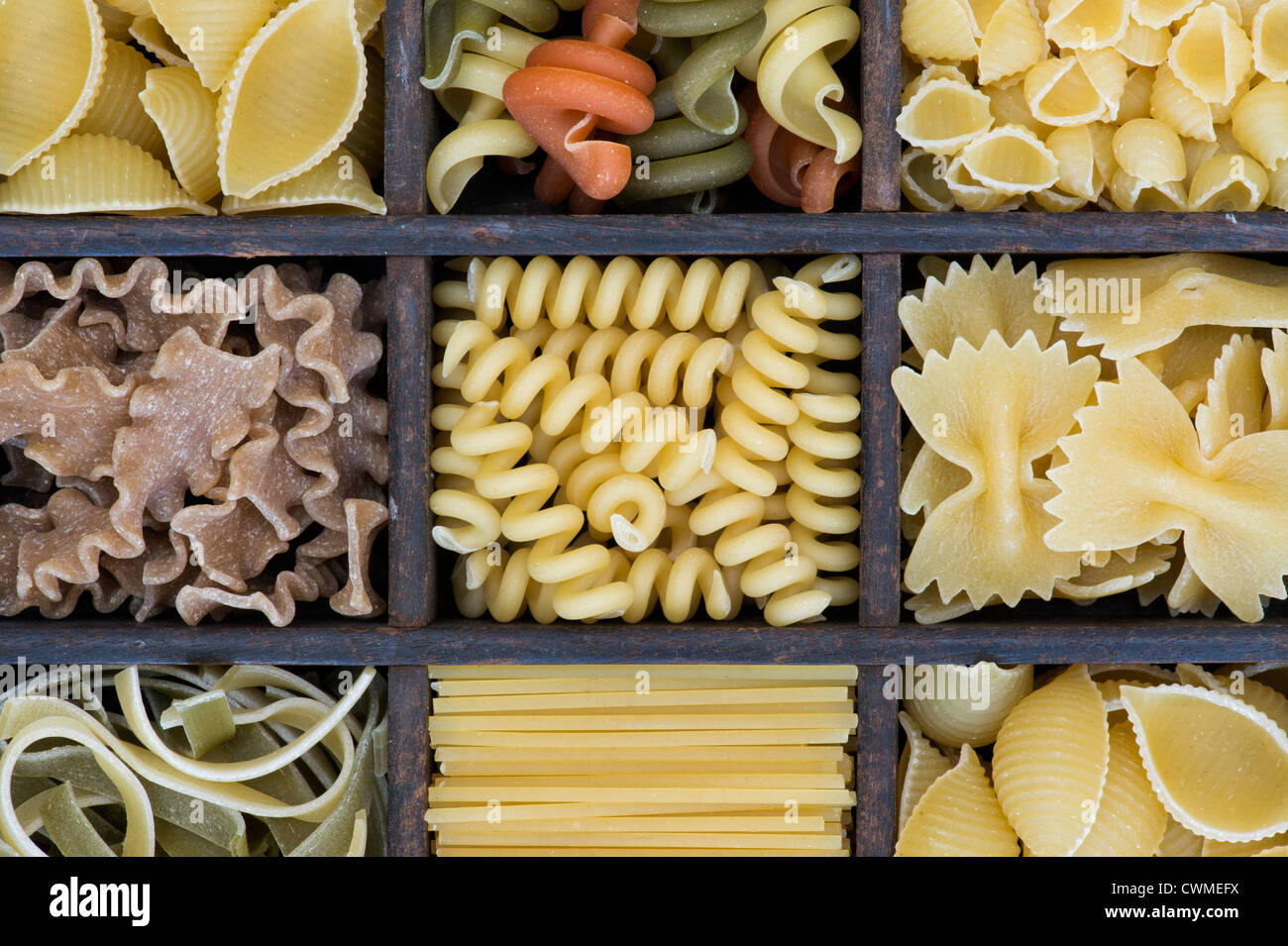 Different types of dried pasta in a wooden tray - Stock Image