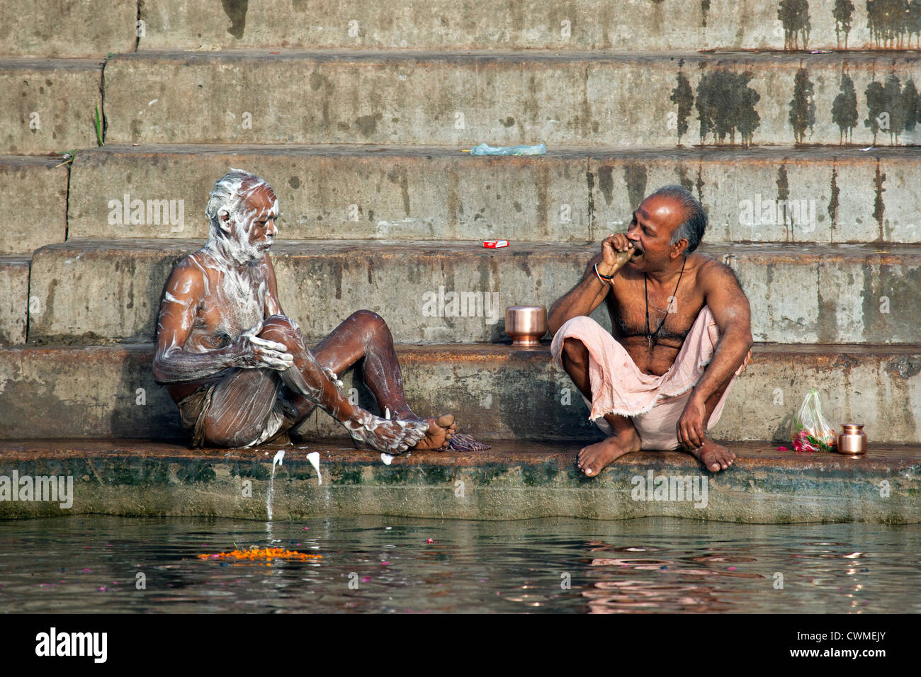 Indian men washing with soap and cleaning teeth at a ghat along the holy Ganges river, Varanasi, Uttar Pradesh, - Stock Image