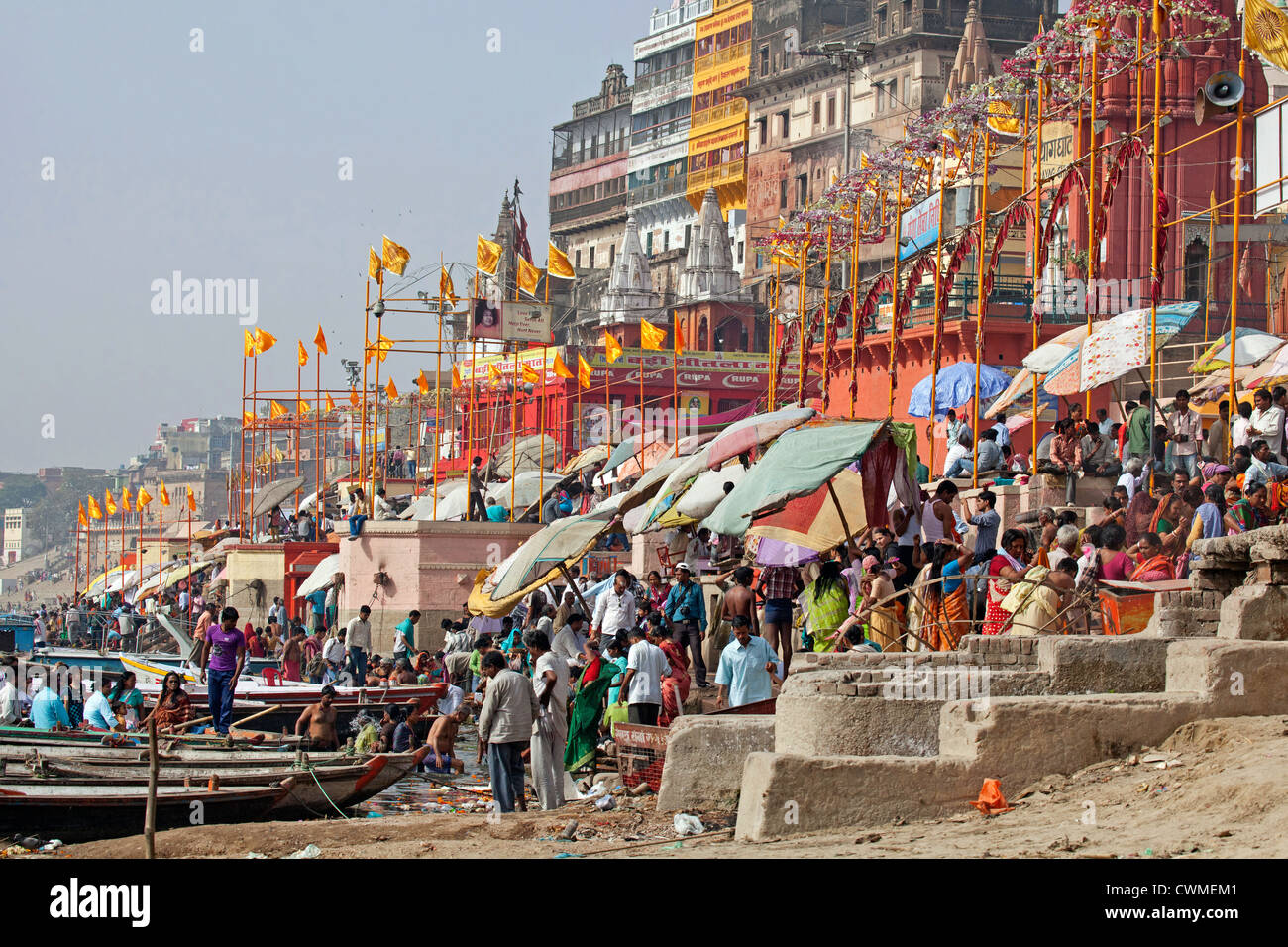 Hindu pilgrims gathering at a ghat to bathe in the Ganges river in Varanasi, Uttar Pradesh, India - Stock Image