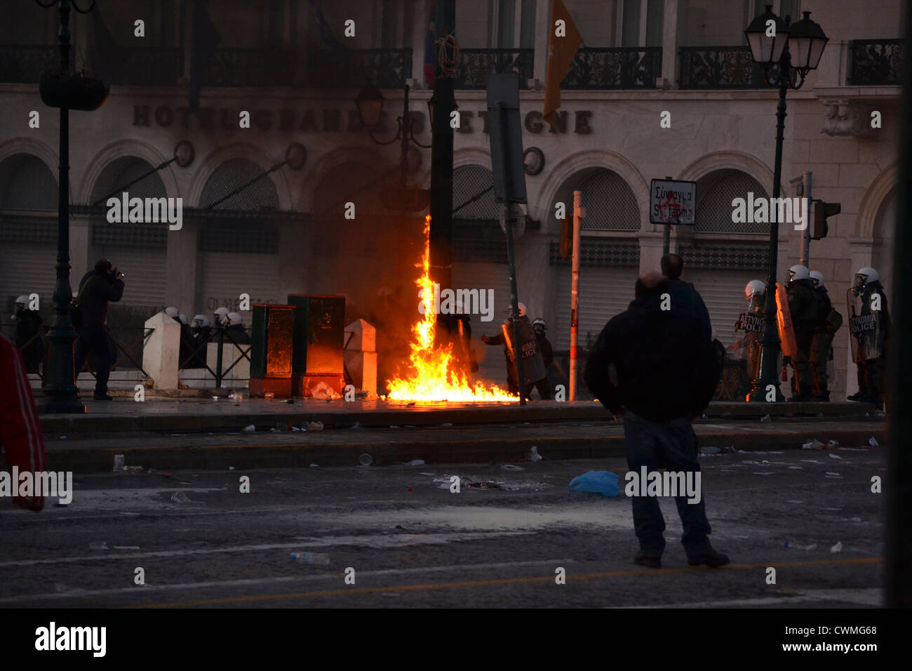 Petrol bombs burn next to riot police during an anti-austerity demonstration in Syntagma Square. Athens, Greece. - Stock Image