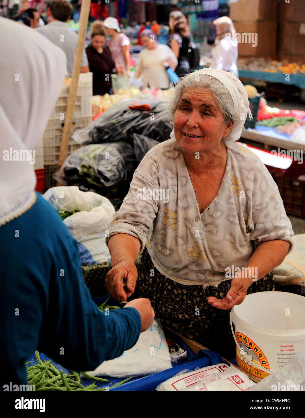 Turkish woman stallkeeper gives change to female customer in market near Dalyan Turkey - Stock Image